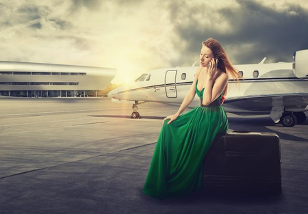 private plane: beautiful woman waiting for flight departure sitting on suitcase talking on mobile phone with airplane on background