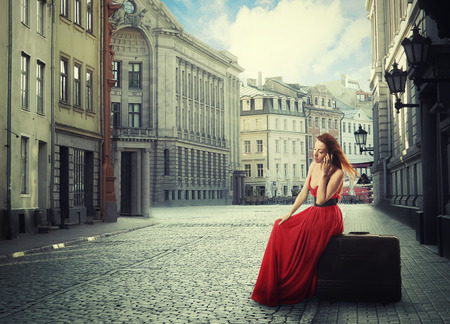 latvia girls: beautiful tourist woman in red dress sitting on suitcase talking on mobile phone on a quiet old town street
