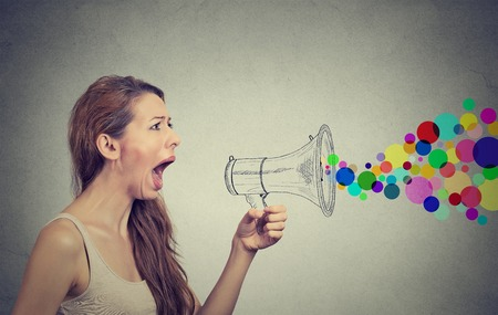 trickster: Portrait angry screaming young woman holding megaphone isolated on grey wall background. Negative face expression emotion feelings. Propaganda, breaking news, power, social media communication concept