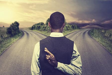 hombre de negocios en frente de dos carreteras que cruzan los dedos con la esperanza de mejor toma de oportunidad Foto de archivo