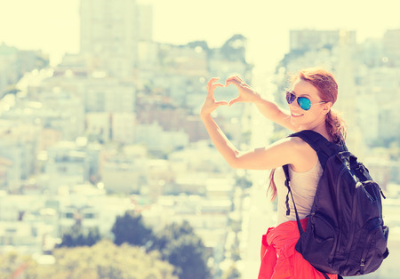 love expression: Young woman in San Francisco city with beautiful beaming smile backlit by warm glow of sun shining down on summer day. Girl with glasses hands shaped like heart. style yellow filter image Stock Photo
