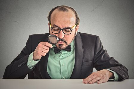 scrutinize: Serious executive man director sitting at desk skeptically looking through magnifying glass at table isolated wall office background. Face expression. Application offer evaluation process concept
