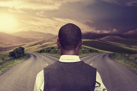 crossroad: hombre de negocios en frente de dos carreteras que espera mejor toma de oportunidad Foto de archivo