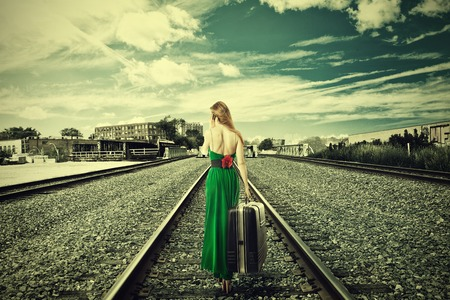 Young woman in blue dress with suitcase walking away on rail tracks talking on mobile phone