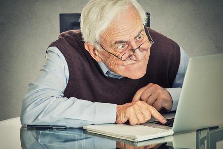 persona confundida: Anciano mayor que usa la computadora sentado en la mesa aislada en el fondo gris de la pared. Las personas mayores y el concepto de la tecnolog�a Foto de archivo