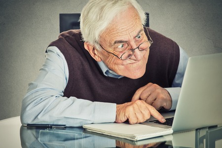 man working on computer: Elderly old man using computer sitting at table isolated on grey wall background. Senior people and technology concept