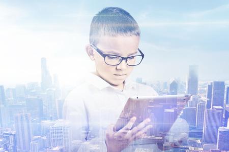 ni�os inteligentes: Ni�o Doble exposici�n y la ciudad. Joven estudiante que usa la tableta digital con horizonte de la ciudad vista rascacielos de fondo. Moderno concepto de comunicaci�n las nuevas tecnolog�as
