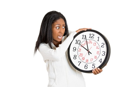 pressured: Closeup portrait woman, worker, holding clock looking anxiously, pressured by lack, running out of time isolated on white background. Human face expression emotion reaction Corporate life concept