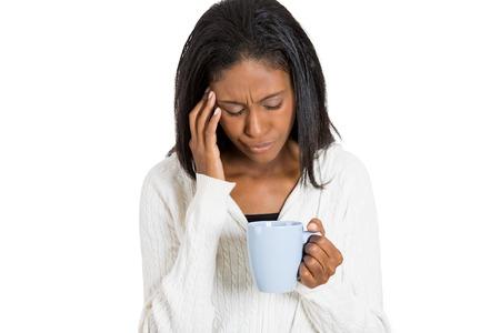 enfermo: Cansado mujer tensionada triste mirando a una taza de caf� aislada en el fondo blanco Foto de archivo