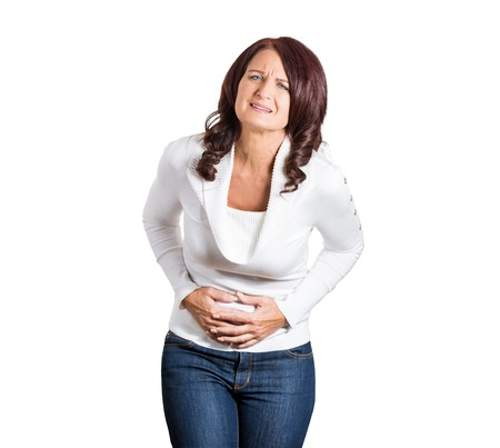 doubled: stressed woman, placing hands on stomach having bad aches and pains, isolated on white background. Face expression
