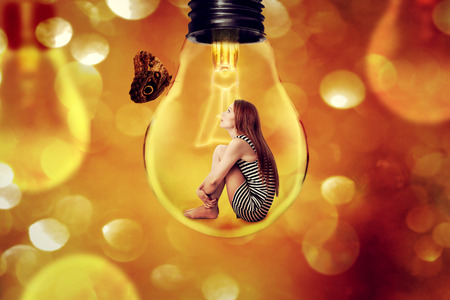 introvert: Lonely woman sitting inside light bulb looking at butterfly isolated on defocused bokeh background