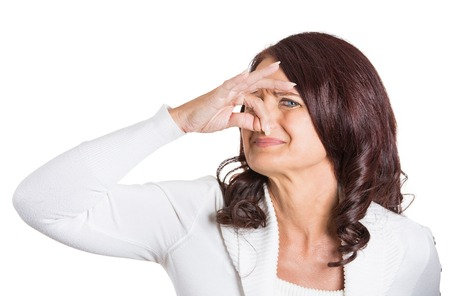Closeup portrait woman covers her nose disgusted something stinks, very bad smell situation isolated on white background. Human face expression Stock Photo