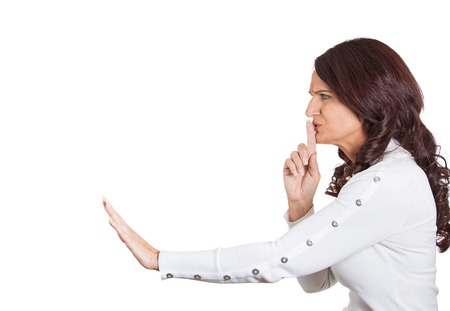 shhh: Side profile serious woman placing finger on lips pointing at someone, shhhhh, quiet, silence Stock Photo