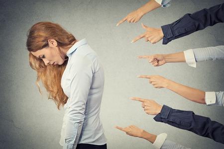 Concept van de aanklacht schuldig zakenvrouw persoon. Zijprofiel trieste verstoord vrouw naar beneden te kijken vele vingers wijzen naar haar geïsoleerde grijze kantoor achtergrond. Menselijk gezicht meningsuiting emotie gevoel