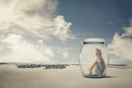 young woman sitting in a jar in the desert. Loneliness outlier concept Foto de archivo
