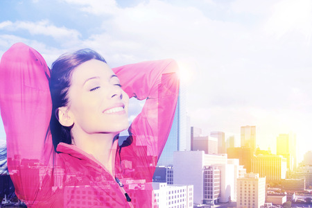 open arms: Double exposure of young joyful beautiful woman over cityscape. City woman happy standing excited elated arms raised in joy taking deep breath celebrating freedom. New York city skyline background