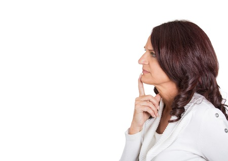 Side profile portrait serious beautiful mature woman thinking finger on lips gesture looking up isolated white background copy space. Human face expression emotion feeling body language perception