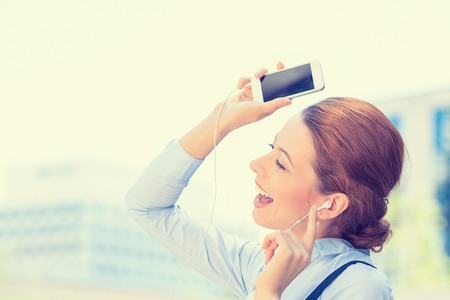 radio active: Closeup portrait attractive smiling business woman walking on street listening music on mobile smart phone outdoor laughing isolated city background. Positive human emotion face expression. Urban life