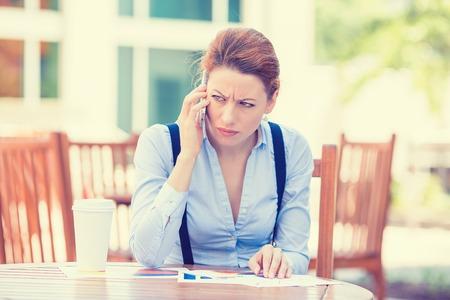 conflictos sociales: Retrato infeliz preocupado medio mujer de negocios de edad hablando por teléfono móvil aislado al aire libre fuera de la oficina corporativa. Negativos sentimientos emoción expresión facial. La vida urbana concepto dificultad estrés Foto de archivo