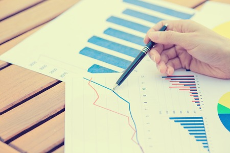 growing: Closeup business woman hands with pen presenting company annual report statement document, papers chart, growing up graph. Stock market, office, tax, education concept. Stock Photo