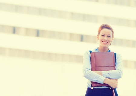 corporate women: portrait of confident smiling happy pretty young professional woman standing on a background of corporate city office. Positive face expression Stock Photo