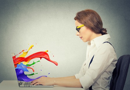 coming out: Side view profile attractive happy young business woman working on laptop computer colorful splashes coming out of screen liquid effect isolated grey wall background. Positive face expression vision