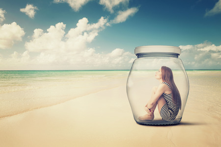 young woman sitting in a glass jar on a beach looking at the ocean view. Loneliness outlier person. After storm survivor message to future generation concept