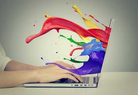 Close-up portret van de handen van zakenvrouw op het toetsenbord met behulp van laptop met kleurrijke spatten, vloeibare effect van beeldscherm computer scherm geïsoleerd op een grijze achtergrond. Creatieve business concept