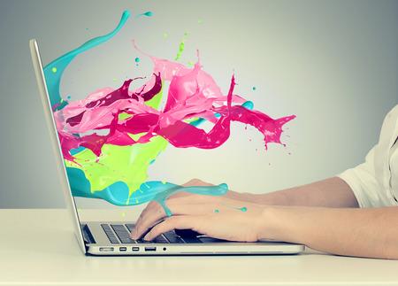 trabajo social: Retrato de detalle de manos de la mujer de negocios en el teclado usando la computadora portátil con toques de colores, efecto líquido fuera del monitor de la pantalla del ordenador la pantalla aisladas sobre fondo gris. Concepto de negocio creativa Foto de archivo