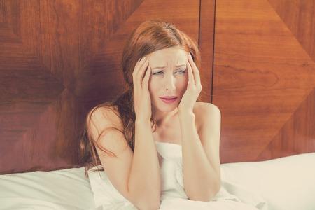 dolor de cabeza: Insomnio vecinos ruidosos concepto de vida estresante. Retrato preocupó a mujer joven que pone en la cama no puede conciliar el sueño dolor de cabeza tiene las manos en los templos. Bienestar Salud Foto de archivo