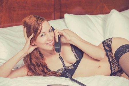 black lingerie: Young happy smiling woman in black lingerie laying in a bed talking making a phone call in a hotel room. Underwear glamour fashion beauty concept