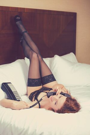 parejas sensuales: Retrato morena joven y bella mujer en ropa interior negro Primer hablando por un teléfono por el que se reclina en la cama de una habitación de hotel. Atractiva chica delgada relajante en el dormitorio. Efecto retro Instagram Foto de archivo