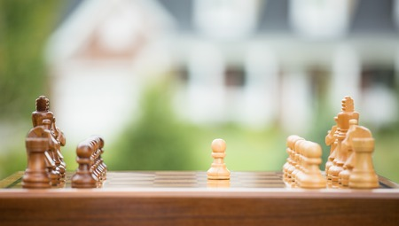 first move: First move over a wood chessboard. Closeup chess game figures isolated outside home background. Real estate sale, home savings, loans market, mortgage plan and residential tax saving strategy concept