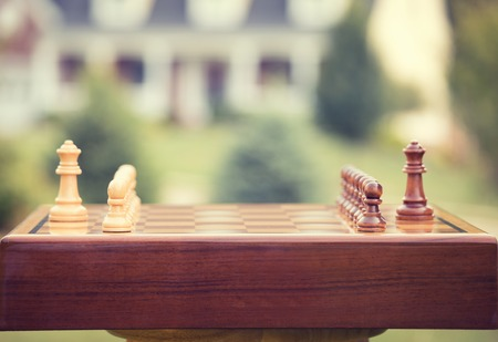 move ahead: First move over a wood chessboard. Closeup chess game figures isolated outside home background. Real estate sale, home savings, loans market, mortgage plan and residential tax saving strategy concept