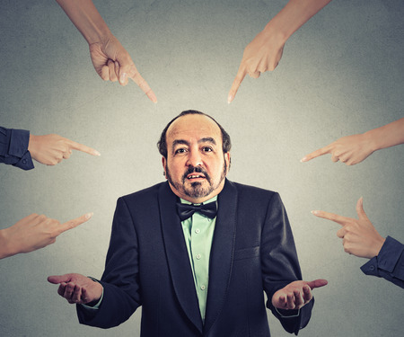 shrugs: Concept of accusation of guilty arrogant businessman. Middle aged man judged by different people many women fingers point at him. Guy shrugs shoulders