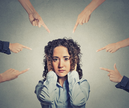 Concept of accusation of guilty businesswoman many fingers pointing at her. Portrait sad unhappy woman covering her ears doesnt want to hear isolated grey office background. Human face expression Stock Photo