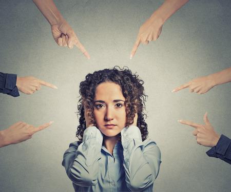 conflictos sociales: Concepto de acusaci�n de la empresaria culpable muchos dedos apuntando hacia ella. Retrato triste mujer infeliz que cubre sus o�dos no quiere o�r aislado fondo gris oficina. Expresi�n del rostro humano