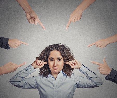 accusation: Concept of accusation of guilty businesswoman. Portrait unhappy sad upset woman plugging her ears many fingers pointing at her isolated grey office background. Human face expression emotion feeling Stock Photo