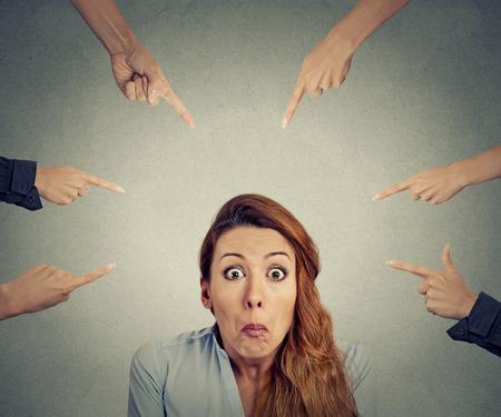 maladroit: Concept d'accusation d'affaires coupable. Portrait confondu femme en col�re de nombreux doigts pointant � son bureau isol� sur fond gris. Expression du visage humain �motion n�gative sentiment