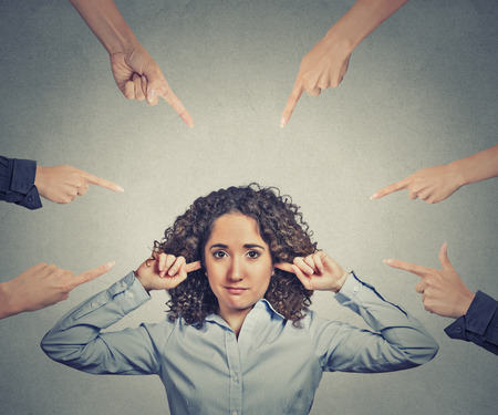 corporate responsibility: Concept of accusation of guilty businesswoman. Portrait unhappy sad upset woman plugging her ears many fingers pointing at her isolated grey office background. Human face expression emotion feeling Stock Photo