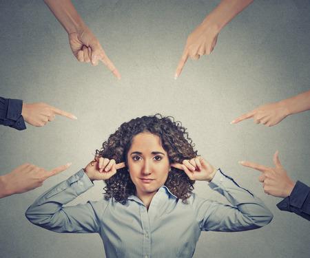 conflictos sociales: Concepto de acusaci�n de la empresaria culpable. Retrato infeliz triste mujer molesta que tapa sus o�dos muchos dedos que se�alan en su gris aislado fondo de la oficina. Rostro humano emoci�n expresi�n sentimiento Foto de archivo