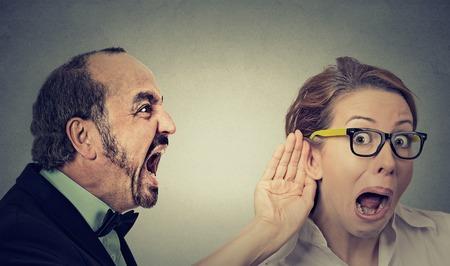あなたは私を聞くことができますか。奇妙な叫びの肖像画怒っている人は、メガネと灰色の壁の背景に分離された耳ジェスチャー リッスンする手の 写真素材