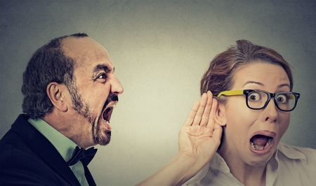 listens: Can you hear me? Portrait angry man screaming curious surprised woman with glasses and hand to ear gesture listens isolated on grey wall background. Human face expressions Stock Photo