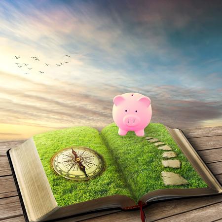 banco mundial: Colegio de ahorro concepto de educaci�n financiera. Ilustraci�n de hucha y el libro m�gico abierto cubierto de hierba verde, la br�jula y la manera sendero empedrado. Fantas�a visi�n del mundo imaginario. Protector de pantalla original. Foto de archivo