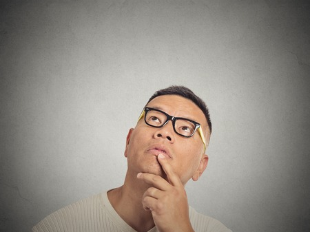 proposito: Retrato hombre guapo pensamiento mirando hacia arriba aislados en el fondo gris de la pared con copia espacio. Expresiones faciales humanas, las emociones, los sentimientos, el lenguaje corporal, la percepción