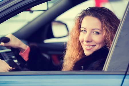 buckled: Side portrait smiling attractive happy winter woman, buckled up driving testing her new car, automobile, purchased at dealership isolated street, city traffic background. Safe driving habits concept