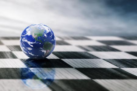 estrategia: mundo en un tablero de ajedrez aislado en el fondo del cielo azul. Foto de archivo