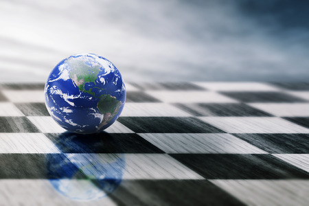 hand globe: world on a chessboard isolated on blue sky background.