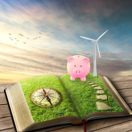 wind force wheel: Wind Generators, Ecology savings. Future of energy industry concept. Opened book with wind turbines installed covered with green grass piggy bank compass. Creative screen saver