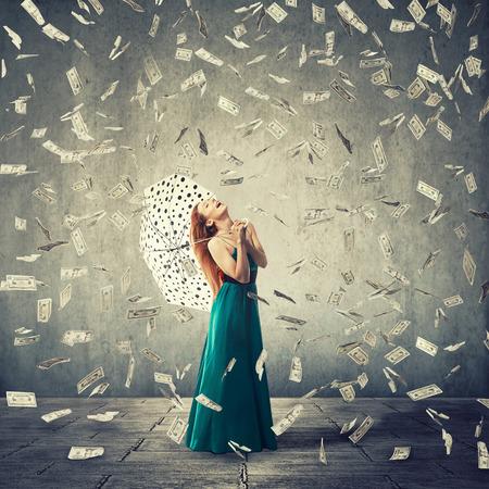dinero: Mujer joven emocionada con el paraguas bajo una lluvia de dinero aislado sobre fondo gris de la pared. Las emociones positivas �xito suerte financiera buen concepto de econom�a Foto de archivo